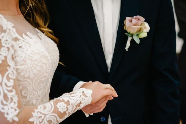 De bruidegom houdt de handen van de bruid vast. gelukkige liefde en vreugdevol huwelijksmoment