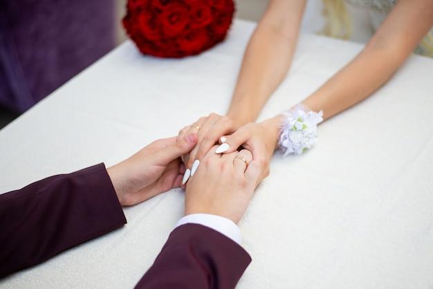 De bruidegom houdt de handen van de bruid vast