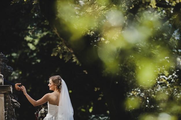 De bruidegom houdt handen zijn bruid