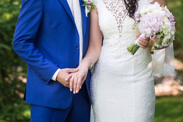 De bruidegom houdt zachtjes de hand van de bruid in een trouwjurk