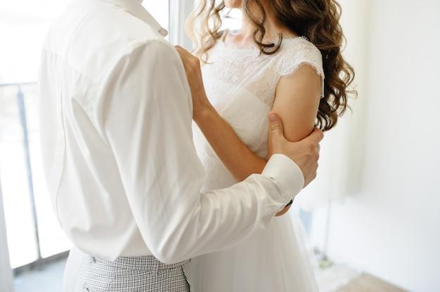De bruidegom houdt zijn bruid bij de schouders. detailopname.