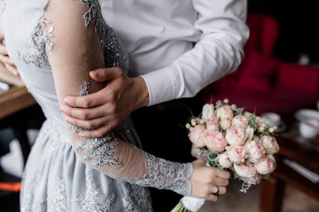 De bruidegom houdt zijn geliefde hand vast