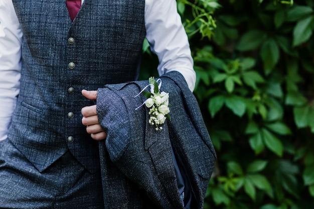 De bruidegom in een pak. een man in een vest houdt een jas in zijn handen