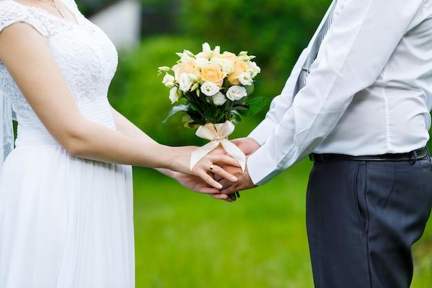 De bruidegom in een pak en de bruid in jurk met boeketten bloemen