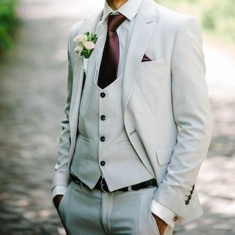 De bruidegom in een pak en stropdas met corsages of knoopsgat op jasje.