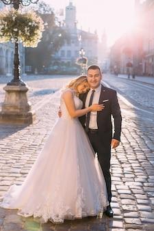 De bruidegom in een stijlvol pak met stropdas omhelst de bruid en kijkt in de camera