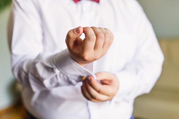 De bruidegom in een wit overhemd bevestigt de manchetknopen aan de manchetten