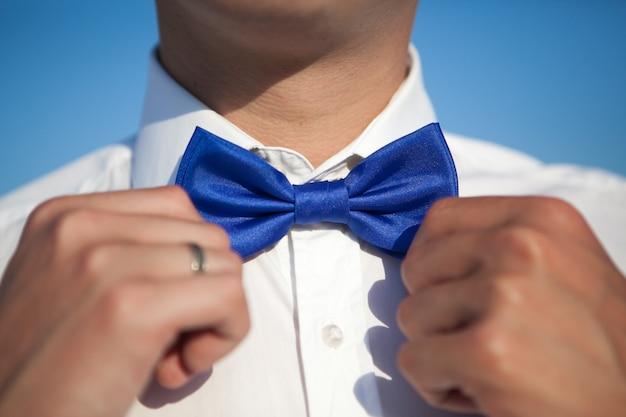 De bruidegom in een wit overhemd maakt een blauwe vlinderdas recht tegen een blauwe hemel