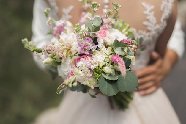 De bruidegom in een wit overhemd met een boeket bloemen in zijn handen omhelst de bruid.