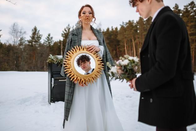 De bruidegom kijkt in de spiegel die de bruid vasthoudt. de bruid draagt een fantastisch beschermend masker.