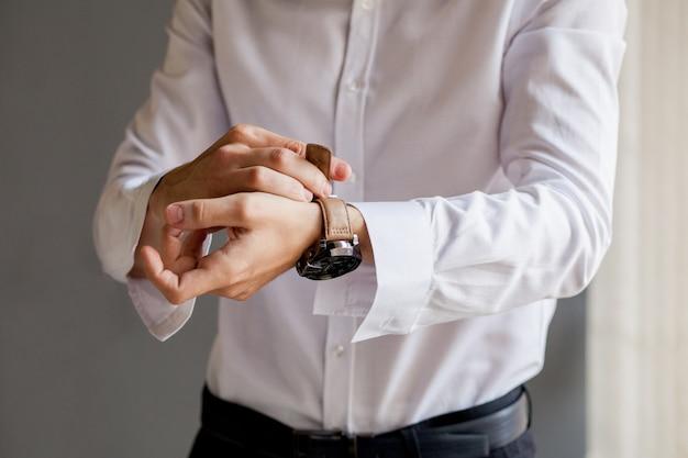 De bruidegom kijkt op zijn horloge om de tijd te controleren. het horloge wordt op de hand van de man gedragen. de voorbereiding van de bruidegom voor de bruiloft