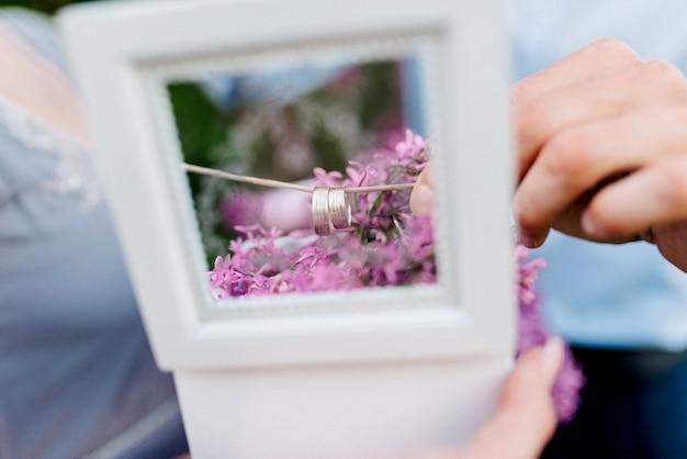 De bruidegom kleedt de bruid met trouwringen bij de lila boog