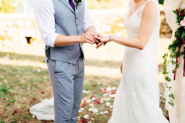 De bruidegom kleedt een ring aan de vinger van de bruid op een bruiloft