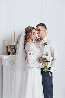 De bruidegom knuffelt de bruid in een kanten trouwjurk in boho-stijl in een gezellige kamer.