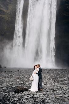 De bruidegom knuffelt de bruid van achter het bruidspaar in de buurt van de skogafoss-waterval, bestemming ijsland Premium Foto