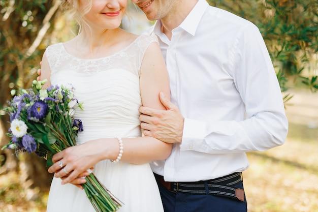 De bruidegom knuffelt de bruid zachtjes bij de groene bomen in de olijfgaard waar de bruid een boeket van vasthoudt