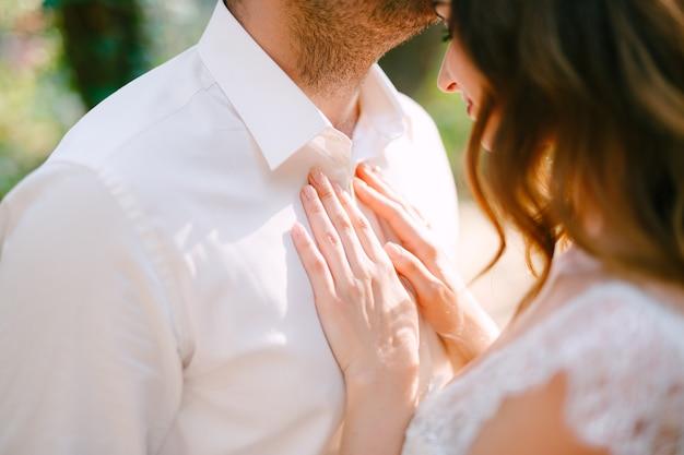 De bruidegom knuffelt zachtjes de bruid op het voorhoofd, de bruid legt haar handen op de borst van de bruidegom Premium Foto