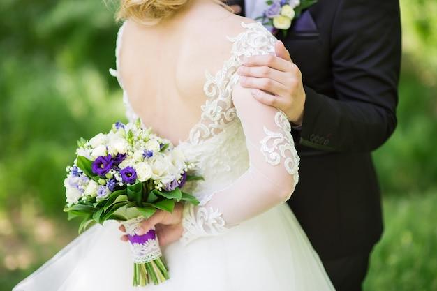 De bruidegom knuffelt zachtjes zijn bruid in de tuin
