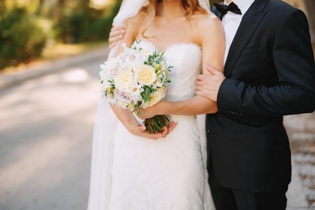 De bruidegom koestert de schouders van de bruid die een bruidsboeket met witte bloemenclose-up vasthoudt