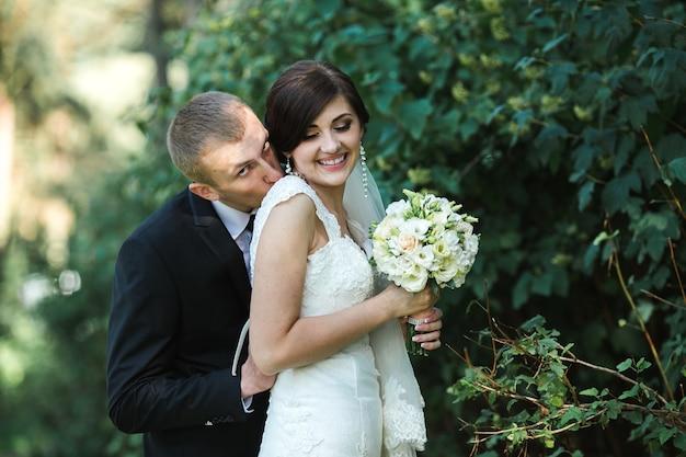 De bruidegom komt achter een mooie bruid staan