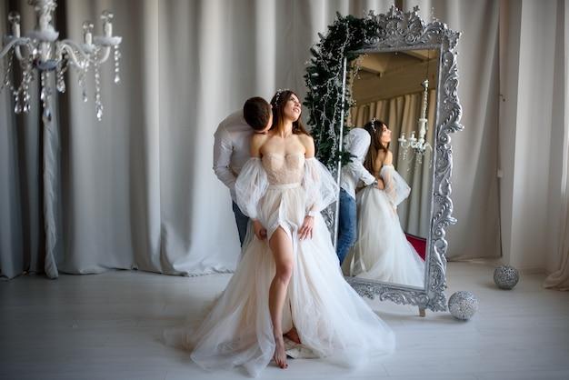 De bruidegom kust de bruid in een trouwjurk