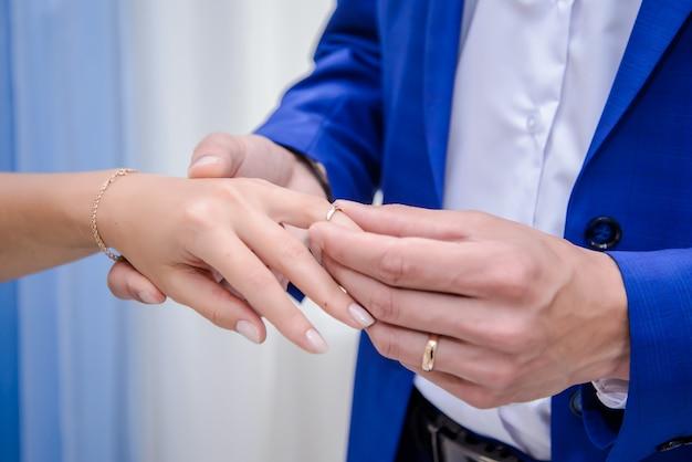 De bruidegom legt de bruidtrouwring aan zijn vinger