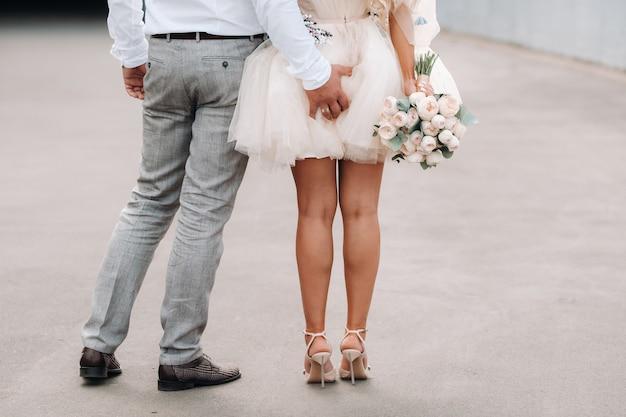 De bruidegom legt zijn hand achter zijn bruid.