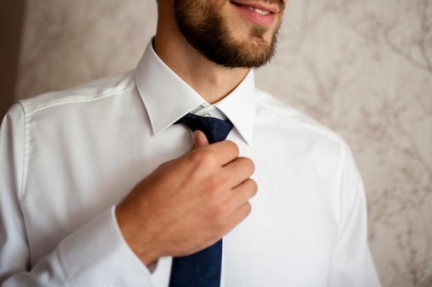 De bruidegom maakt stropdas strik recht