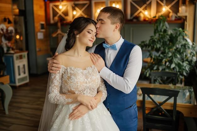 De bruidegom omhelst de bruid bij de schouders en kust haar voorhoofd. liefde, bruiloft concept. gelukkig pasgetrouwde stel.