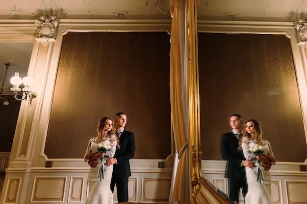 De bruidegom omhelst de bruid en ze kijken uit het raam. de weerspiegeling van de pasgetrouwden in een grote spiegel.