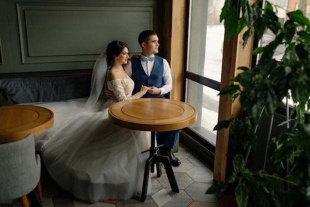 De bruidegom omhelst de bruid en ze kijken uit het raam mooie elegante paar pasgetrouwden verliefd in een loft interieur. bruiloft concept. gelukkig pasgetrouwde stel.