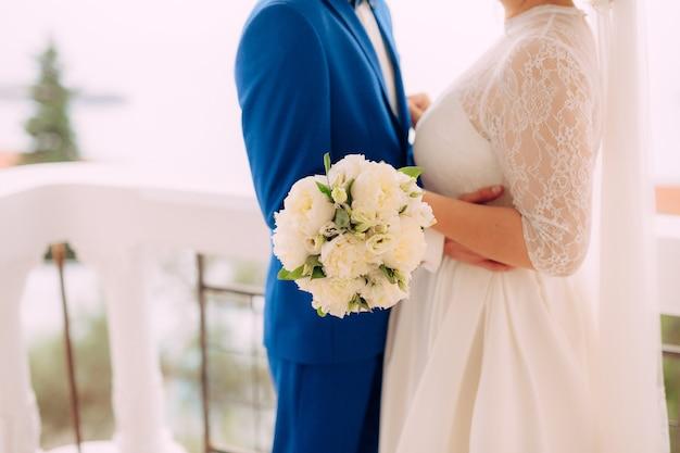 De bruidegom omhelst de bruid op het strandhuwelijk in montenegro
