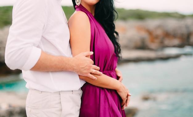 De bruidegom omhelst de bruid op het strandhuwelijk