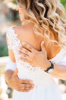 De bruidegom omhelst de bruid stevig, de handen van de bruidegom op de rug van de bruid