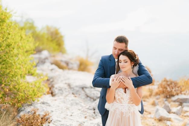 De bruidegom omhelst de bruid zachtjes bij de schouders