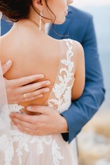 De bruidegom omhelst de bruid zachtjes en streelt haar rug met zijn handen