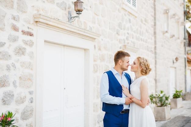 De bruidegom omhelst de bruid zachtjes tegen de achtergrond van een prachtig wit huis in perast.