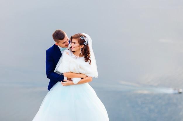 De bruidegom omhelst en kust de bruid op de achtergrond van de rivier
