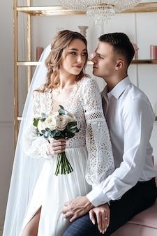De bruidegom omhelst zachtjes de bruid in een prachtige kanten jurk met een boeket verse bloemen.