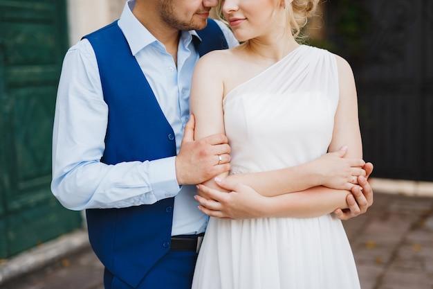 De bruidegom omhelst zachtjes de bruid van achteren, de bruid sloeg haar armen over elkaar