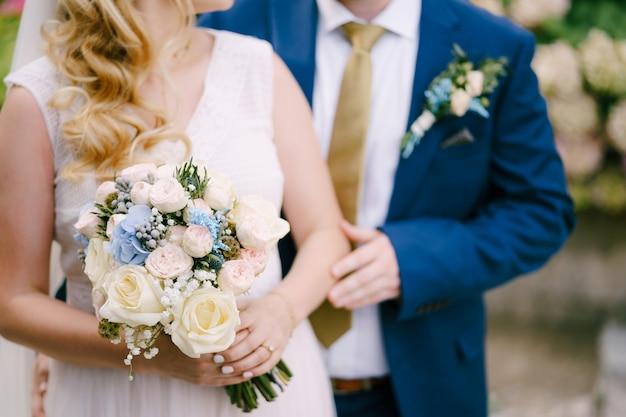 De bruidegom raakt zachtjes de hand van de bruid aan die het boeket vasthoudt tijdens de huwelijksceremonie