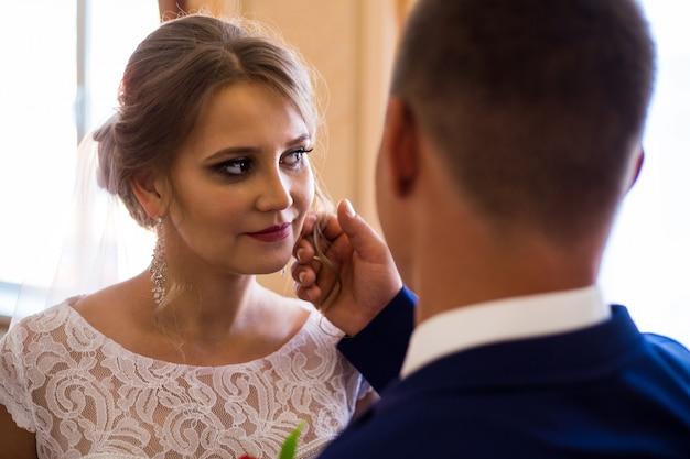 De bruidegom streelt zachtjes de wang van de bruid. vergadering van de bruid en bruidegom
