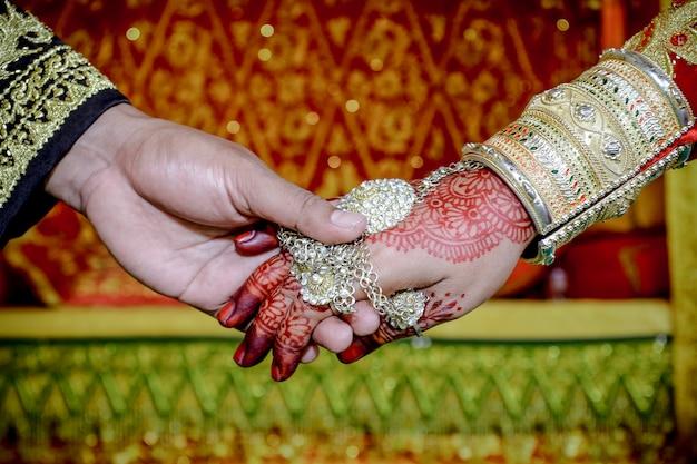 De bruidegom trekt de hand van de bruid