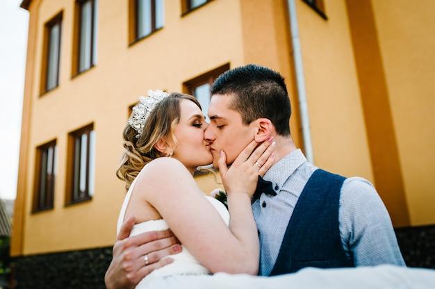 De bruidegom verhoogd en draait bruid. pasgetrouwden zoenen.