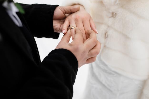 De bruidegom zet in openlucht de trouwring op van zijn toekomstige vrouw