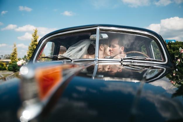 De bruiden kussen de auto op de trouwdag