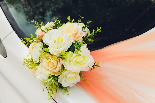 De bruids decoratie van het huwelijksboeket op luxe witte auto.
