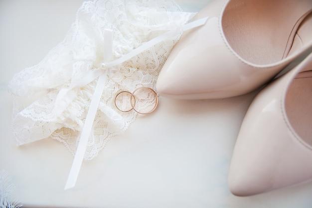 De bruidsschoenen, kouseband en trouwringen van de mooie bruid