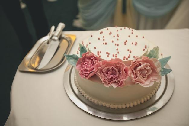 De bruidstaart is versierd met roze bloemen.