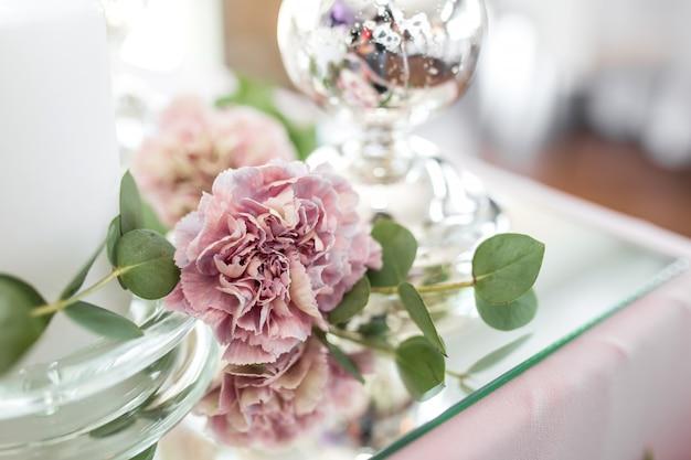 De bruiloftstafeldecoratie voor de pasgetrouwden is versierd met verse bloemen